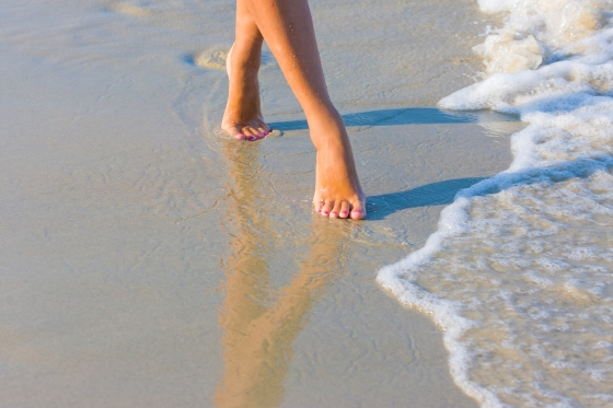 Female leg walking on the beach in the ocean - Narrow depth of f