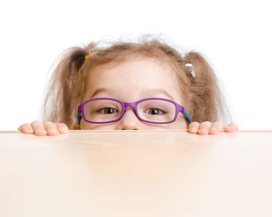 Funny girl in eyeglasses hiding behind a table